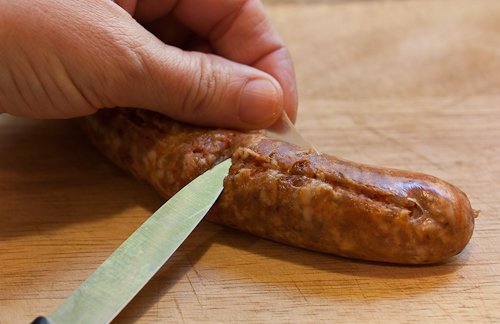 With the tip of a sharp knife, make a long slit in the sausage casing